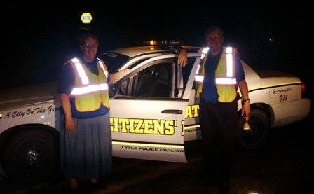 A man and woman in reflective vests stand outside a citizens auxiliary vehicle